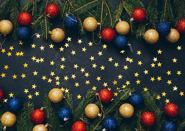 空のスペースで黒の背景に緑のモミとクリスマスのおもちゃのフレーム。フラット横たわっていた。上面図 Premium写真