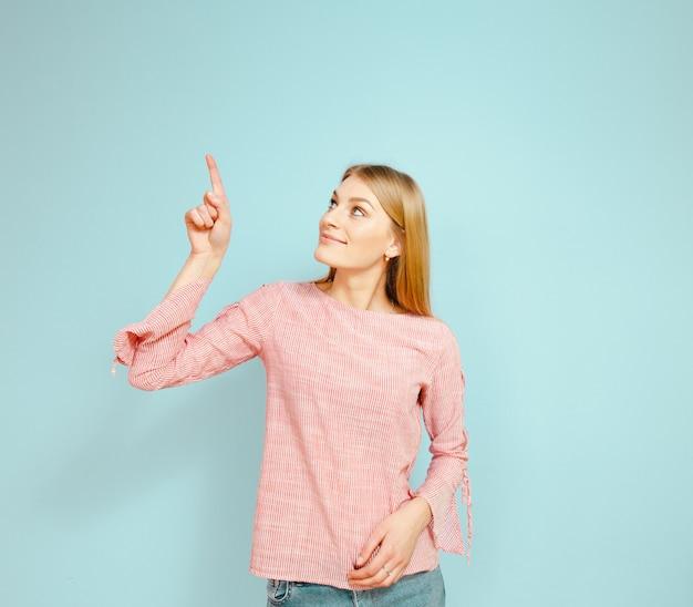 青色の背景にジェスチャーを示す美しいブロンドの女の子。 Premium写真