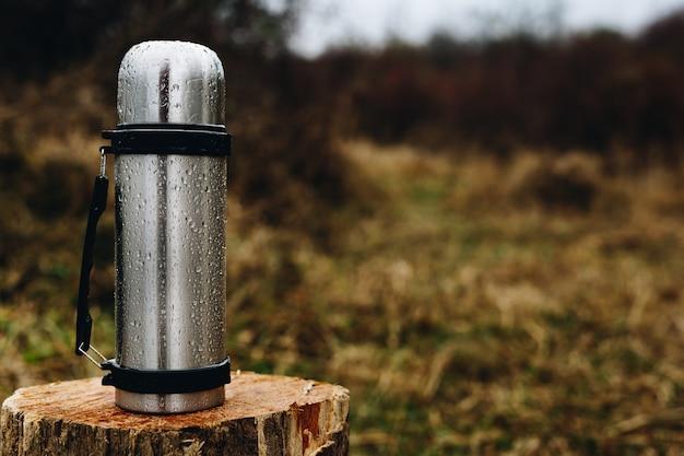 森の中の木の丸太の上に立って魔法瓶。テキスト用のスペース Premium写真
