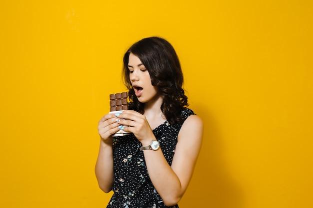 官能的な魅力的な若い女性を食べると黄色の壁に分離された驚くチョコレート Premium写真