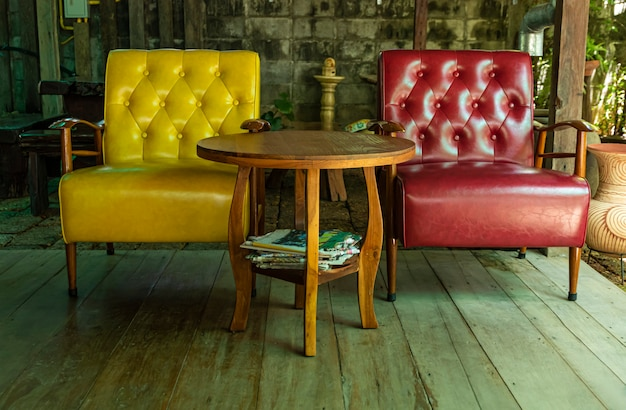 テラスの木製の床に黄色のソファと赤いソファ。 Premium写真