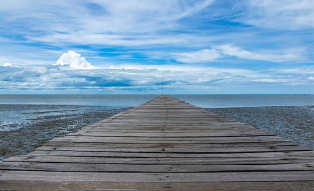 海と青い空の長い木製の通路の端 Premium写真