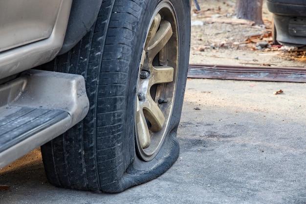 駐車中の車の破損したタイヤのクローズアップ。 Premium写真