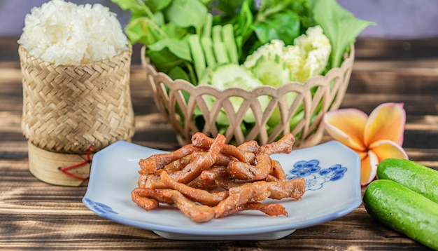 揚げ太陽乾燥豚肉と木のテーブル背景にもち米。 Premium写真