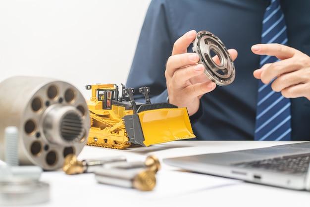 プロのメカニックエンジニアが油圧ピストンポンプのバルブプレートを検査し、オフィスでの作業中にレポートを書き込む、修理メンテナンス重機コンセプト Premium写真