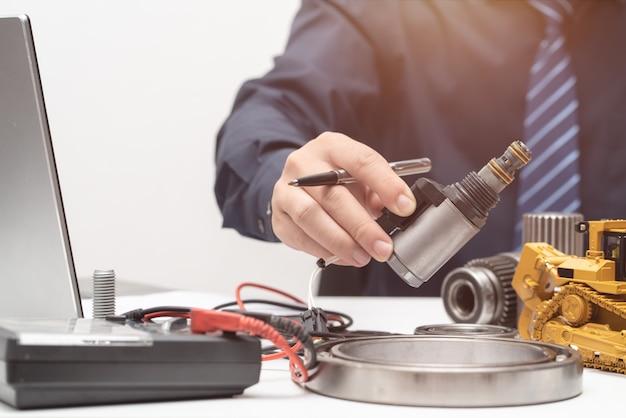 プロのエンジニアがオフィスでの作業中にソレノイドバルブに手を伸ばして、修理メンテナンス重機コンセプト Premium写真