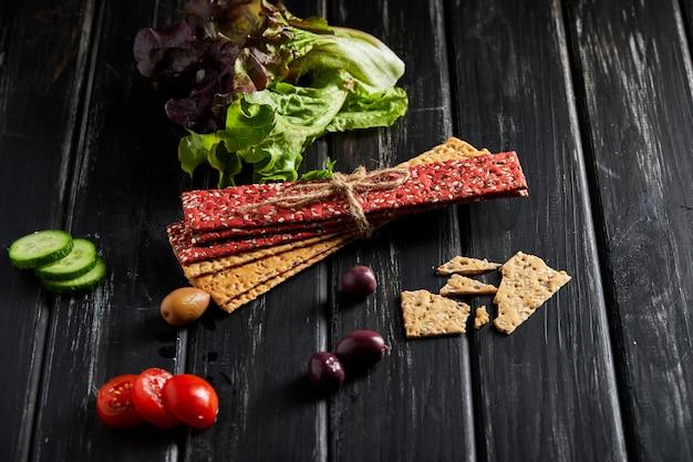 Крекеры из свекольной и ржаной муки с овощами для приготовления закусок на черной стене. вегетарианство и здоровое питание Premium Фотографии