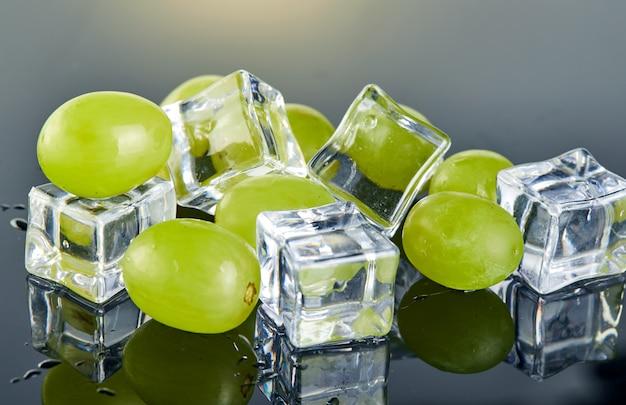 水滴と灰色の背景にアイスキューブと新鮮な緑のブドウ Premium写真