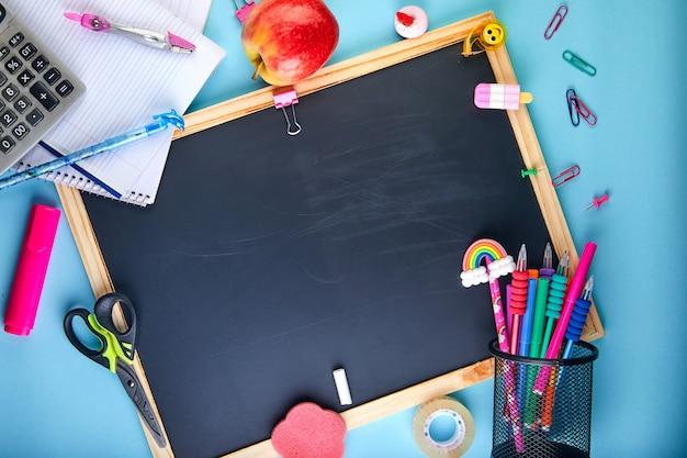 教室の鉛筆、ノート、本、はさみのアクセサリーと学校の背景に戻る Premium写真