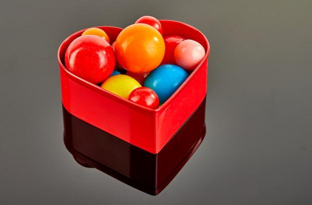 反射と赤いハートの灰色の背景にチューインガムの複数の色のボール。 Premium写真