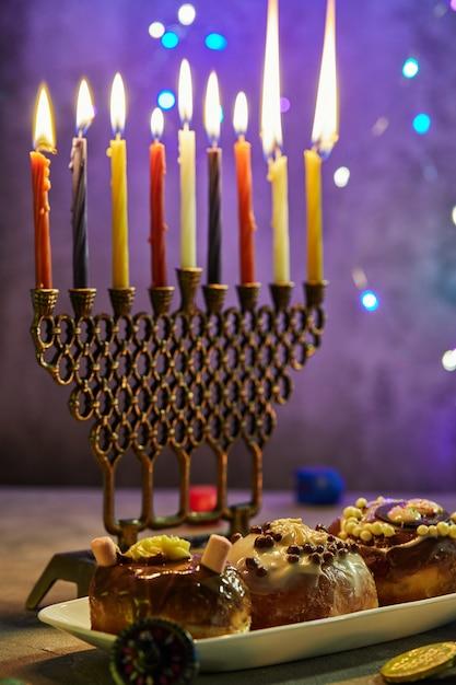 ユダヤ人の祝日のハヌカの背景。伝統的な料理は甘いドーナツです。ハヌカのテーブルは、ろうそくでろうそく足を設定し、青い照明ハヌカのろうそくの上にこま Premium写真