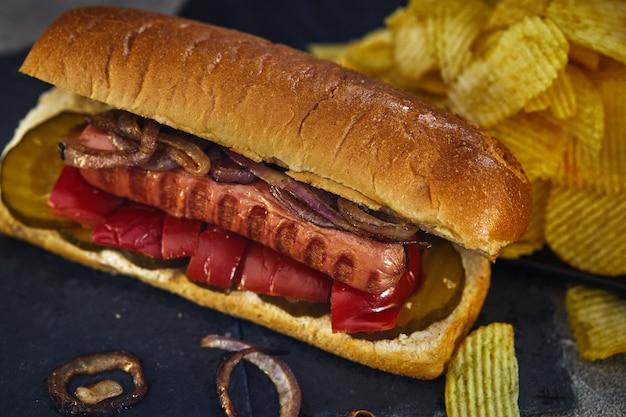 ホットドッグ-きゅうり、赤唐辛子、玉ねぎを入れたパンに入れたホットソーセージ Premium写真