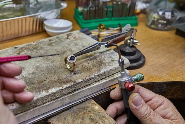 ジュエリー制作宝石商は金の指輪を作ります。 Premium写真
