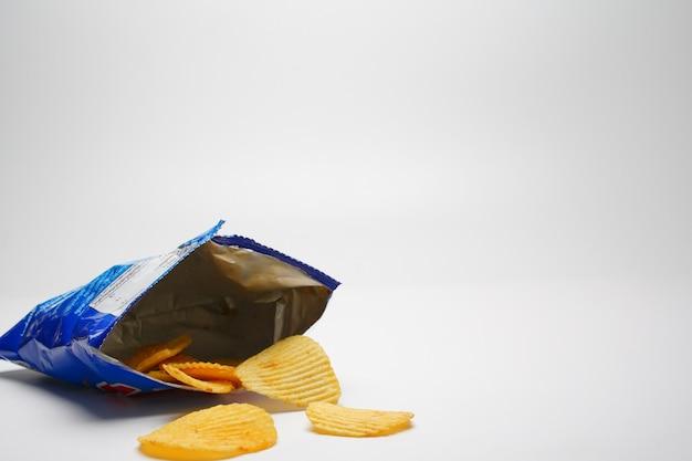 フライドポテトチップは、白い背景の青いビニール袋を開けてこぼれます。 Premium写真