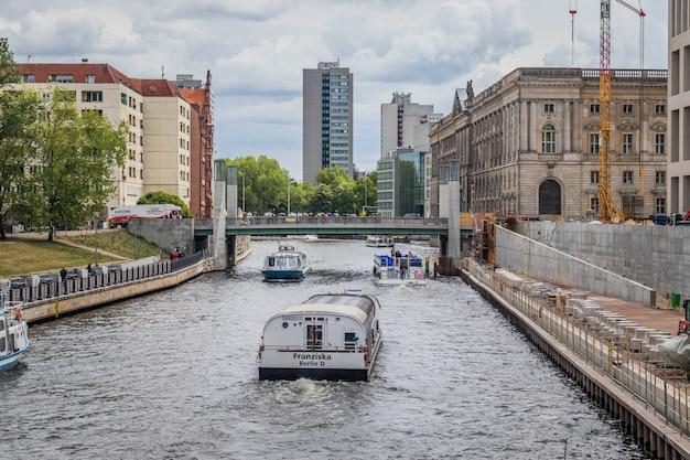 ミッテ地区のシュプレー川の観光船。ベルリン、ドイツ。ヨーロッパ旅行。 Premium写真