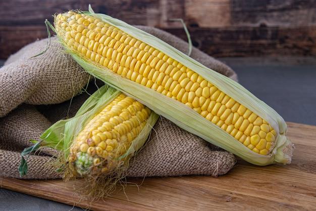 Органическая сахарная кукуруза, свежая кукуруза, собранная в деревянные ящики. урожай кукурузы, производство кукурузы, органическое сельское хозяйство, производство продуктов питания и выращивание овощей. Premium Фотографии