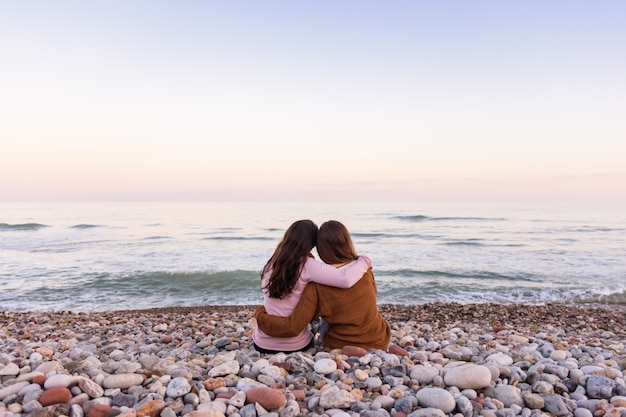 Несколько лесбиянок сидят на пляже и смотрят на красивый закат вместе Premium Фотографии