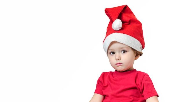 新年に赤いスーツとサンタ帽子で物思いにふける少女。赤ちゃんはクリスマスの贈り物を待っています。 Premium写真