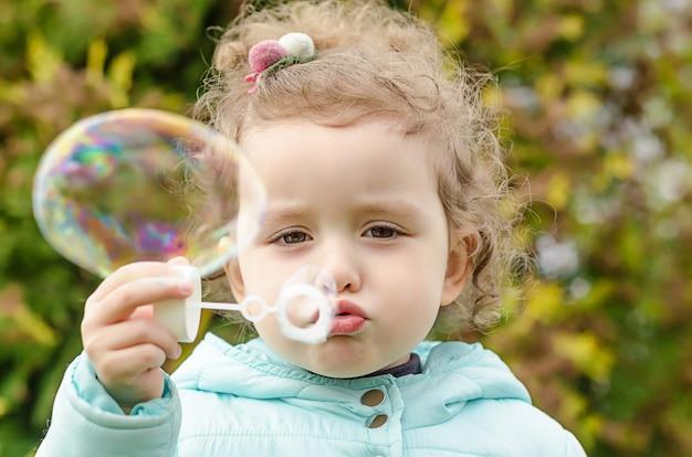 シャボン玉を吹く美しい少女のポートレート、クローズアップ。子供のレジャー。面白い屋外ゲーム Premium写真
