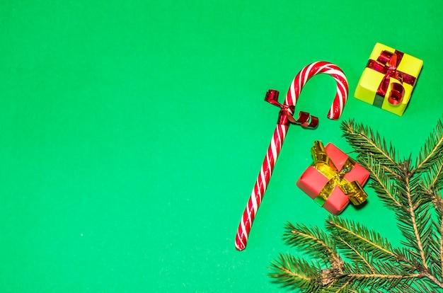 新年、休日、お祝いのコンセプト。緑の背景の贈り物。クリスマスツリーの贈り物、キャンディー杖。平干し、コピースペース Premium写真