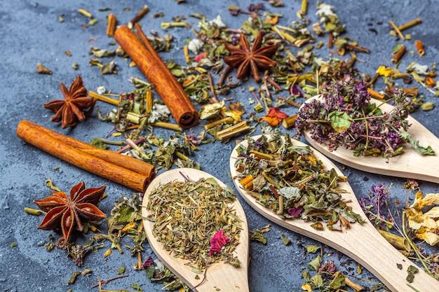 素朴なスタイルの木製のスプーンで別のお茶と生姜、アニス、シナモンの品揃え。茶道のための乾燥した花びらが付いている有機性ハーブ、緑および紅茶。フラットレイアウト、コピースペース Premium写真