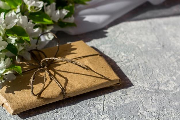 Цветущие ветви вишни, яблони на сером фоне. цветочная композиция. милая подарочная коробка обернутая с коричневой крафт-бумагой и украшенная джутом, взгляд сверху, с космосом для текста. Premium Фотографии