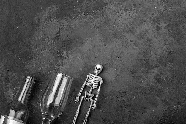 アルコール消費による人格破壊の概念。人間の骨格、ワイングラス、ボトル。アルコール中毒と飲酒。 Premium写真