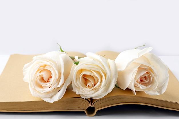 テキストまたはレタリングのためのスペースを持つ白いバラで飾られた空白の開いている日記。手紙、願い、目標、計画、人生の物語を書くの概念。 Premium写真