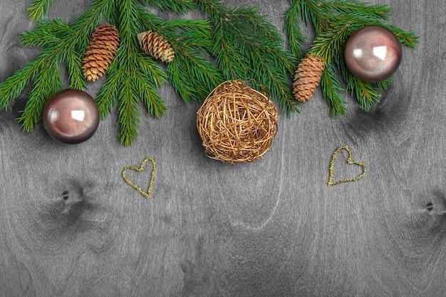 はがき、カバー、バナーのクリスマス組成。モミの枝とボール、素朴な木製の背景にコーン。クリスマス、冬休み、新年のコンセプト。クローズアップ、テキスト用のスペースをコピーします。 Premium写真