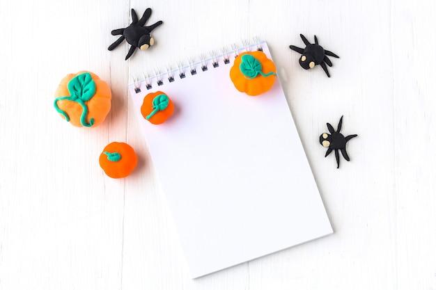 Украшение хеллоуина: тыквы и пауки ручной работы от пластилина и тетради с космосом для текста на белой деревянной предпосылке. Premium Фотографии