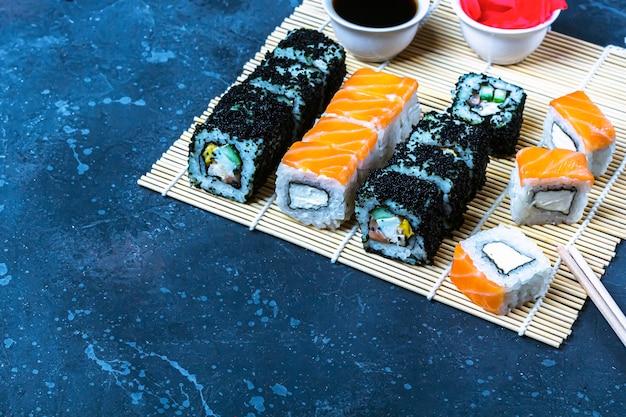 Набор суши-роллов с лососем и омлетом, тофу и овощами, икра летучей рыбы, темпура на макису. традиционная японская еда. Premium Фотографии