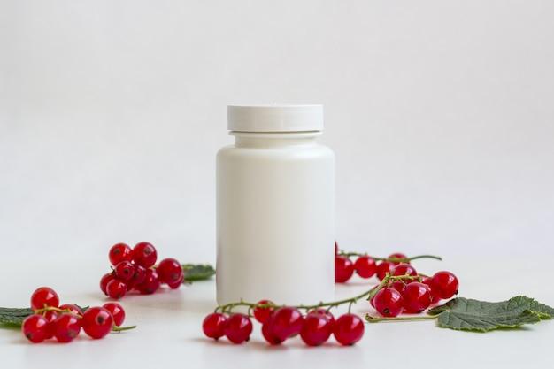 果実の中の錠剤またはビタミン栄養補助食品の白い薬瓶 Premium写真