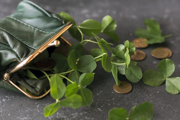 緑の財布からの新鮮なクローバーの葉と金貨は暗い背景に散在しています。聖パトリックの日のコンセプト。 Premium写真