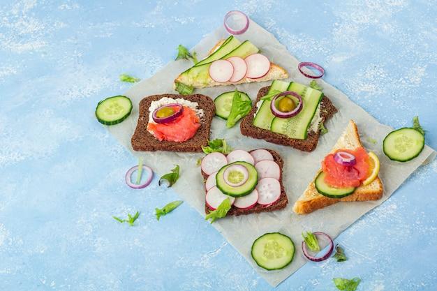 前菜、さまざまなトッピングのオープンサンドイッチ:青の背景に紙の上のサーモンと野菜。伝統的なイタリア料理またはスカンジナビアのスナック。健康的な食事 Premium写真
