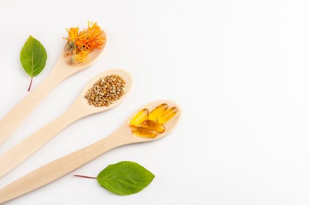 Травяные капсулы, натуральные витамины, сухие цветки календулы на деревянной ложкой на белом фоне. концепция здравоохранения и нетрадиционной медицины: гомеопатия и натуропатия. Premium Фотографии