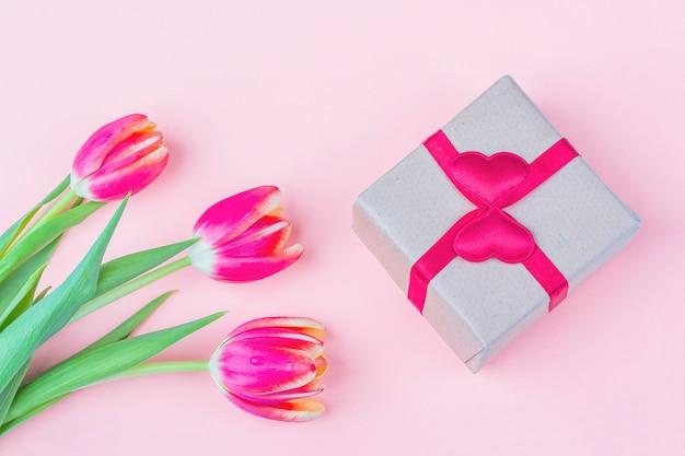 新鮮な赤いチューリップの花と白い背景のギフトボックスの花束。休日の国際女性の日、母の日、バレンタインの日、誕生日、記念日、その他のイベントでの女性への贈り物。 Premium写真