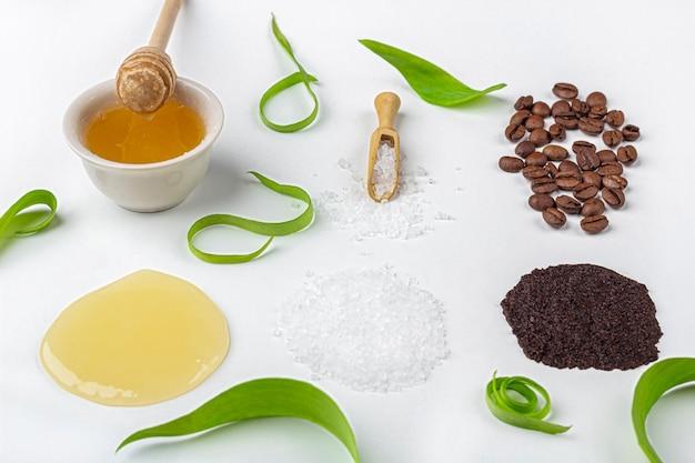 天然オーガニック素材の自家製スキンケア。クレンジングと栄養化粧品。美容製品:白い背景の上の緑の葉の間でクリーム、蜂蜜、コーヒースクラブ Premium写真