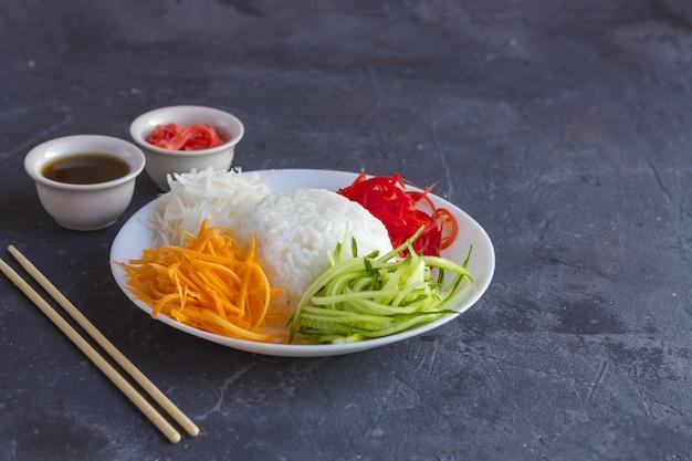 Азиатская еда: белый рис и овощи (морковь, огурцы, дайкон) на темном Premium Фотографии