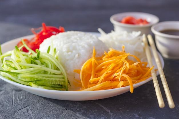 Азиатская еда: белый рис и овощи (морковь, огурцы, дайкон) на темном фоне крупным планом. Premium Фотографии