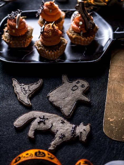 Необычные хэллоуин еда партии стол с тыквой кекс сдобы и печенье. Premium Фотографии