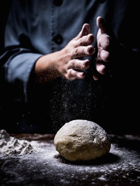 Рука шеф-кондитера, посыпая белой муки над сырой тесто на кухонном столе. Premium Фотографии