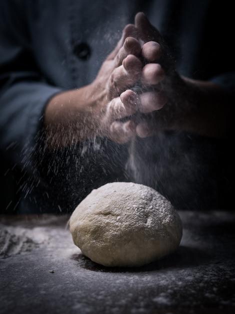 パティシエの手が台所のテーブルに生の生地の上に白い小麦粉を振りかけます。 Premium写真