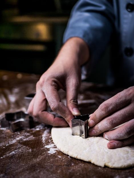Кондитерская рука использует форму для резки теста для печенья на кухонном столе. Premium Фотографии