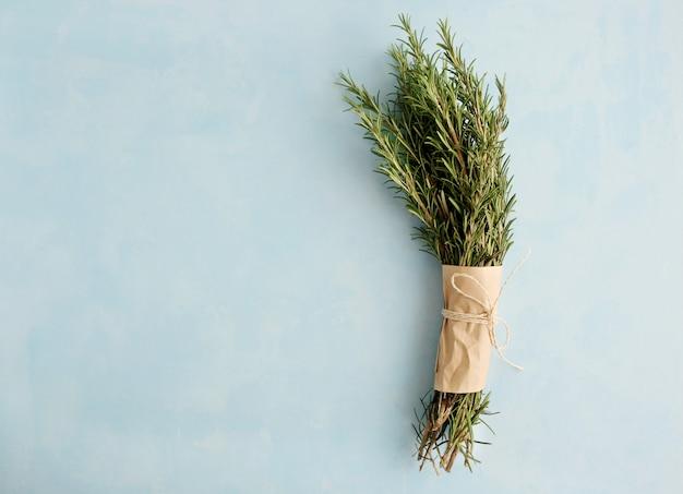 ローズマリーの新鮮な緑の小枝の束は紙に包まれ、ロープで縛られて、青色の背景にあります。 Premium写真