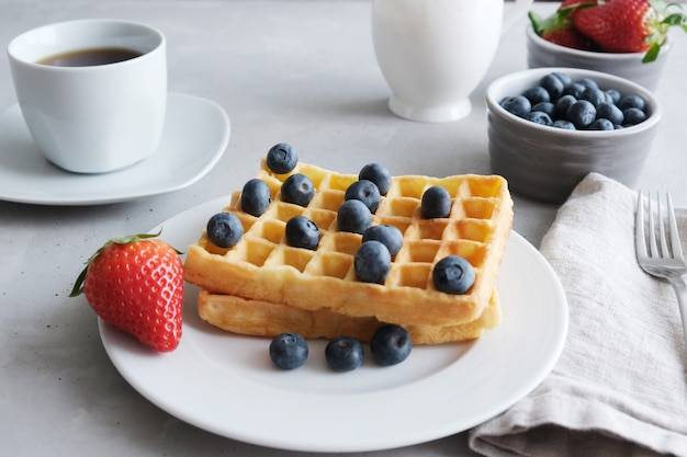 ブルーベリーとイチゴの白い皿に新鮮な自家製ウィーンまたはベルギーワッフル Premium写真