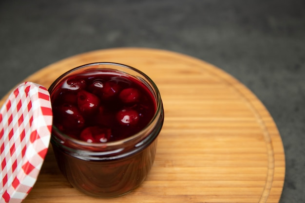 木の板、板に赤い色の開いたふたが付いているガラス瓶の中のチェリージャム。 Premium写真