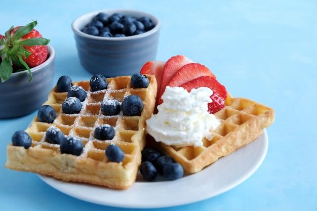 バイオイチゴとブルーベリーと青色の背景にホイップクリームと新鮮なウィーンの自家製ワッフル。 Premium写真