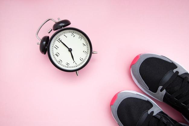 レトロな黒の目覚まし時計とピンクの背景にラズベリースニーカーと黒。 Premium写真