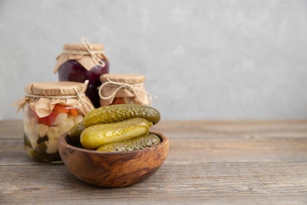 漬物、塩漬け、発酵キュウリは、木製のテーブルの上に木製のボウルにあります。 Premium写真
