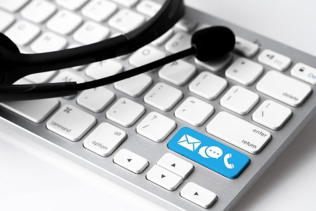 Свяжитесь с нами значок на клавиатуре с наушниками и микрофоном Premium Фотографии